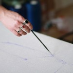 Художник рисует кистью набросок картины